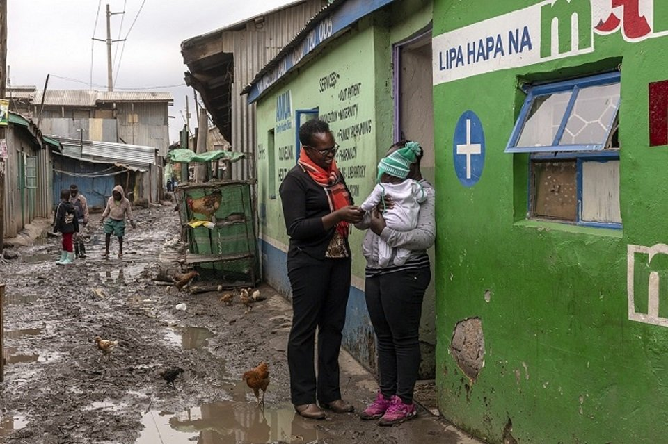 Transformational Business Network - Josephine Suleyman talks to a mother outside her Olive Health Care Centre, Sinai slum, Nairobi, Kenya